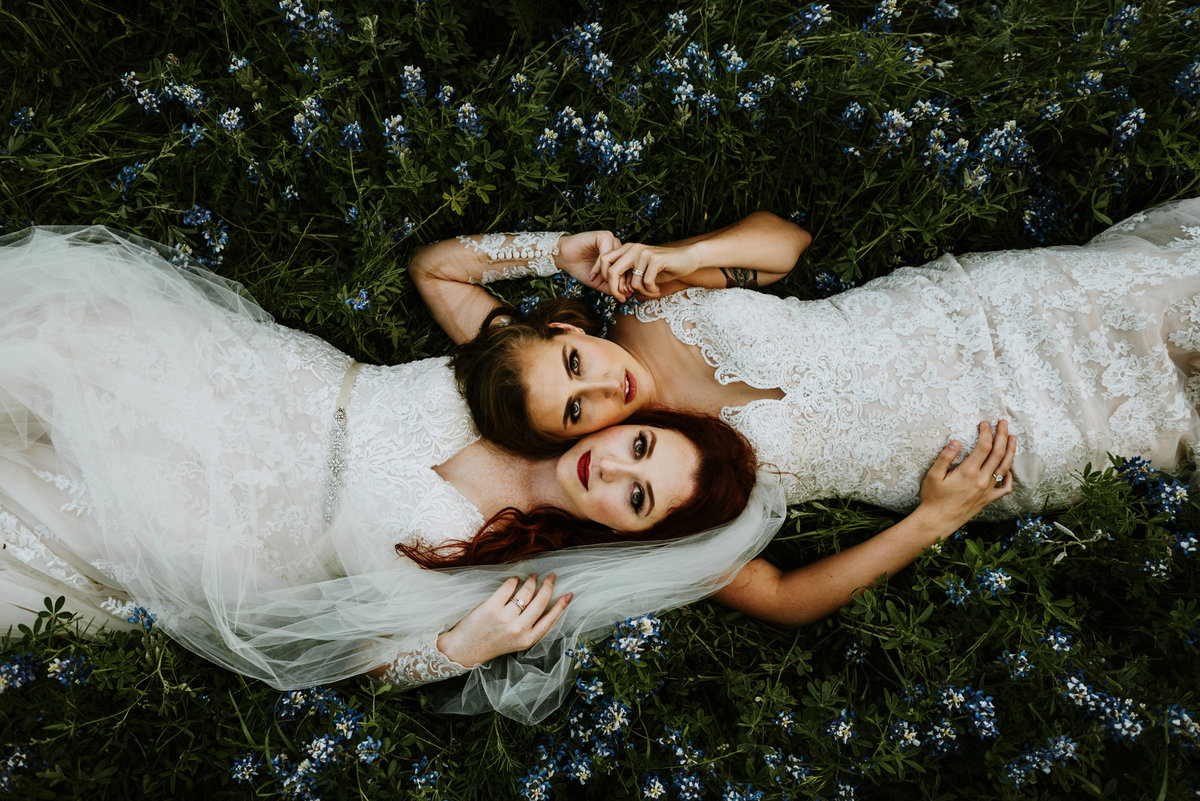two brides laying in wildflowers