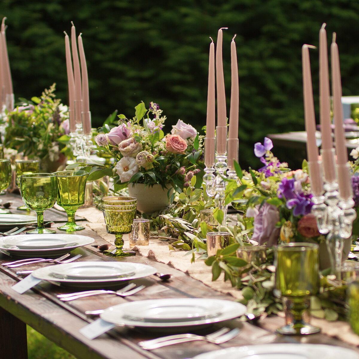 Rustic Wedding reception decor with  pink, peach, purple  and green floral centrepieces on a wooden table outdoors.