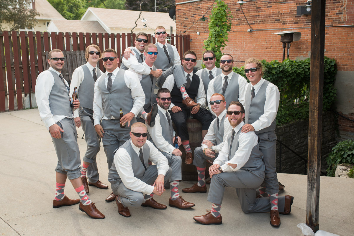groomsmen pose outside smiling