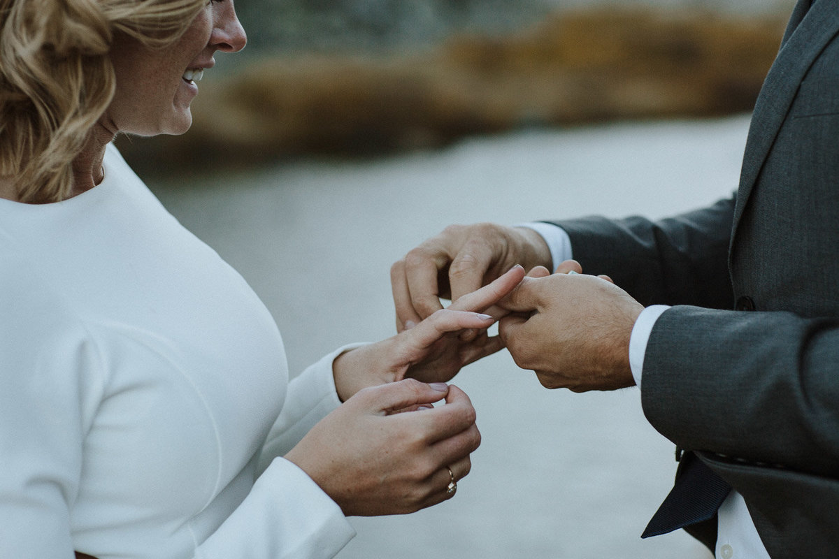A groom places a ring on a bride's finger during an outdoor elopement ceremony in the mountains