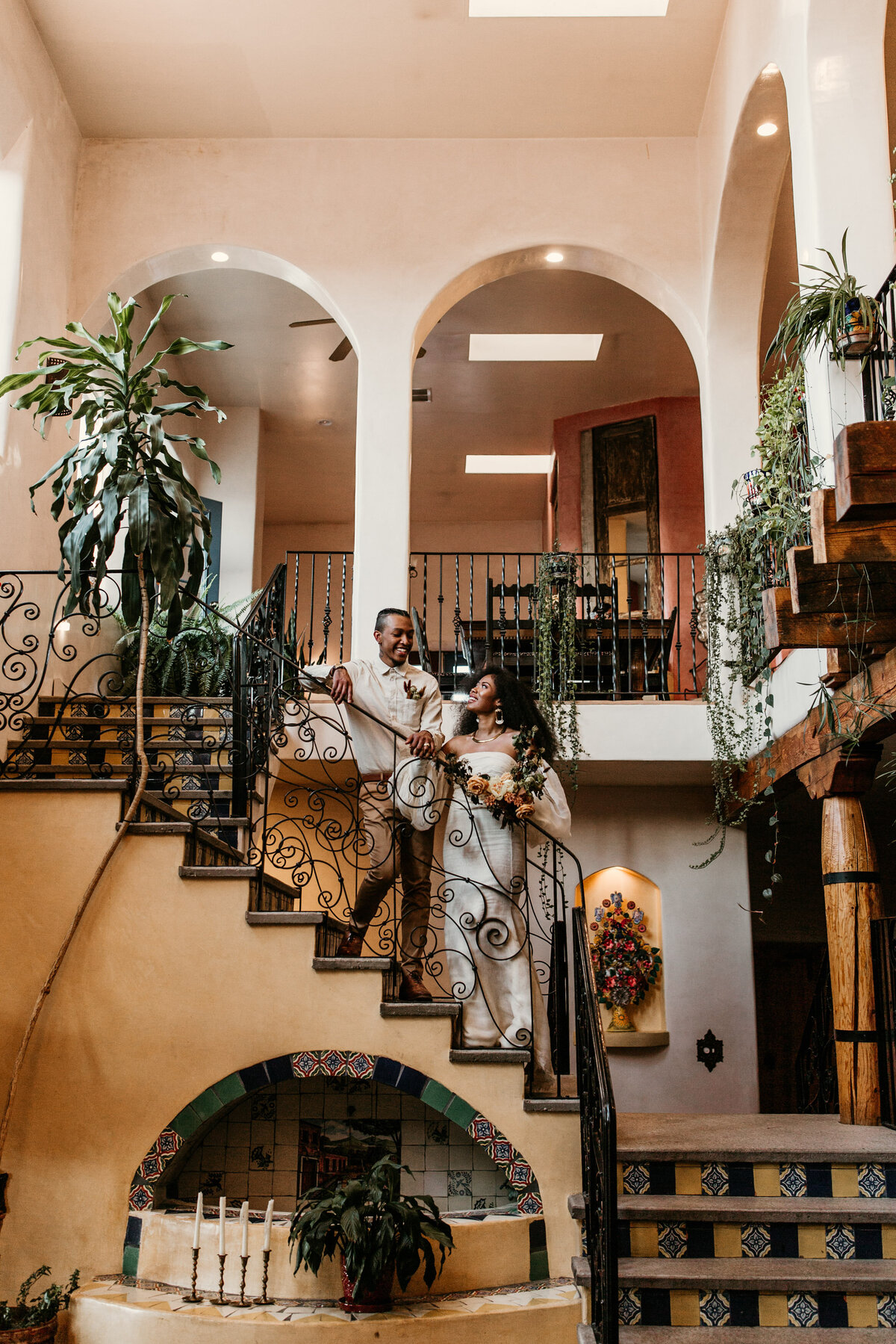 Bride and groom standing on a southwest staircase in Santa Fe venue
