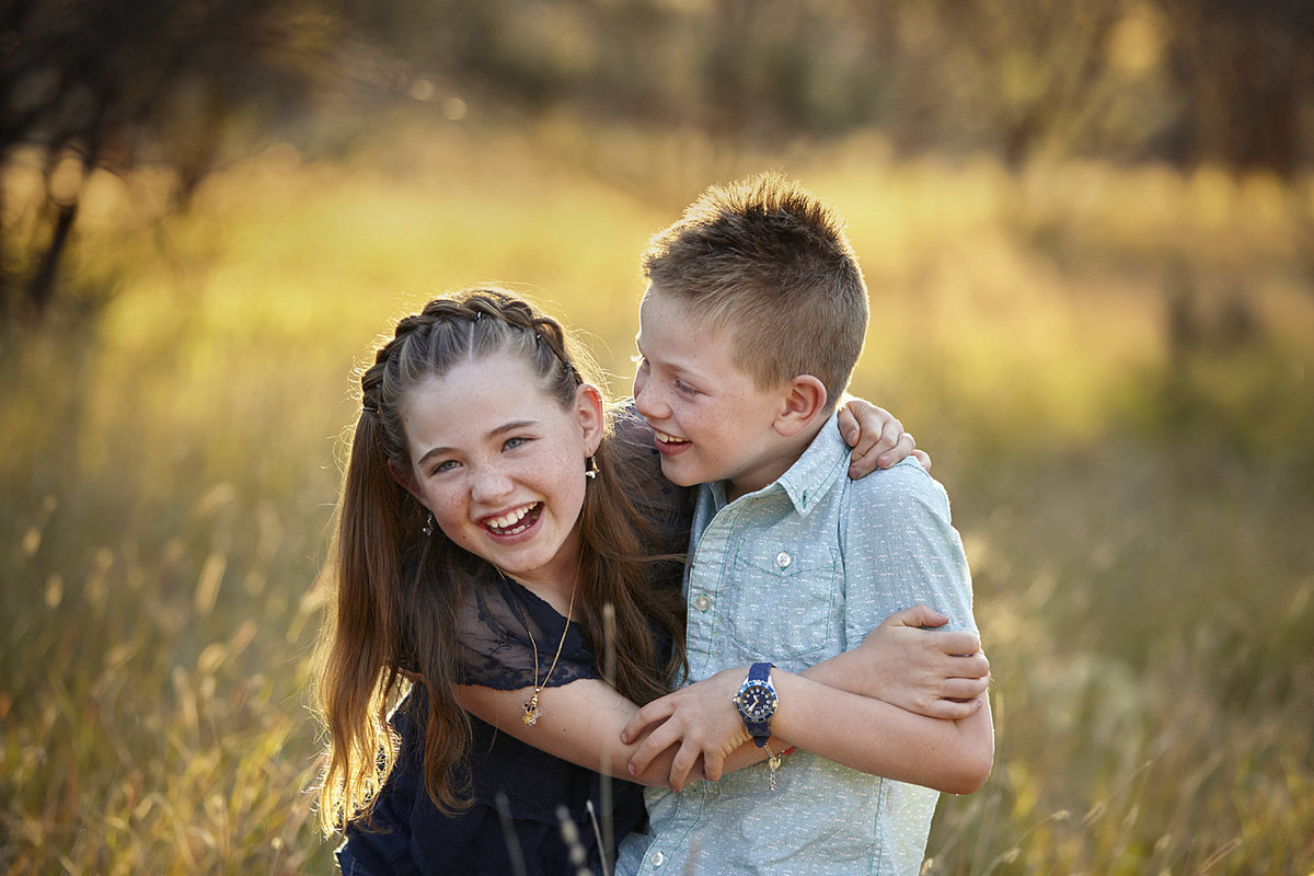 Boy and girl cuddling into each laughing in golden sunlight