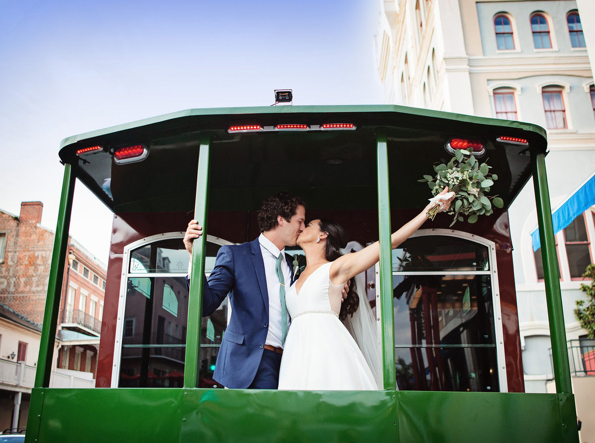 NOLA destination bride and groom kissing in the back of a streetcar in the French Quarter