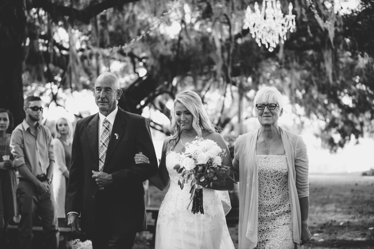 Emotional moment for the bride as her parents walk her down the aisle. Seven hills farm wedding photographer in gainesville florida.
