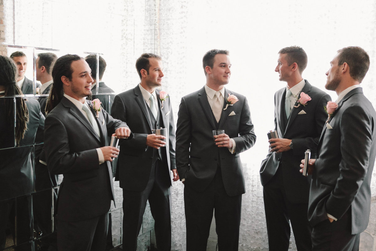 Groomsmen talk while holding whiskey drinks at The Allure wedding in La Porte Indiana