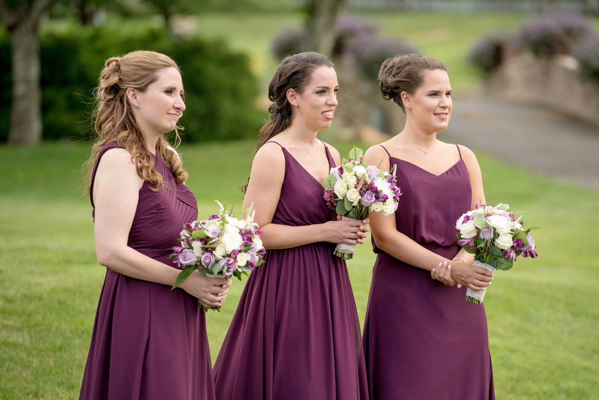bridesmaids in burgundy during wedding ceremony on the golf course at Willow Creek Golf and Country Club
