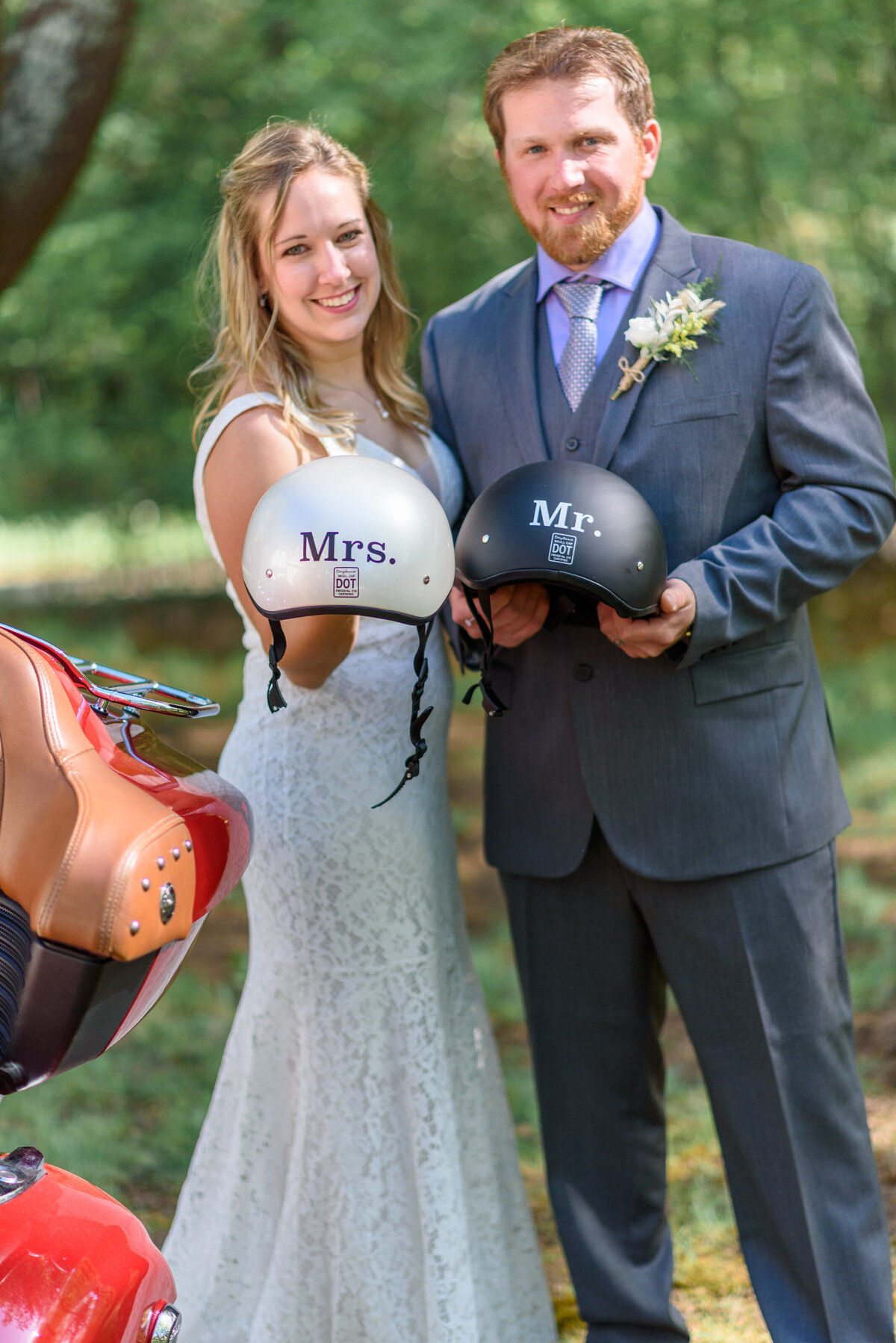 Bride and groom at New Hampshire wedding holding motorcycle helmets