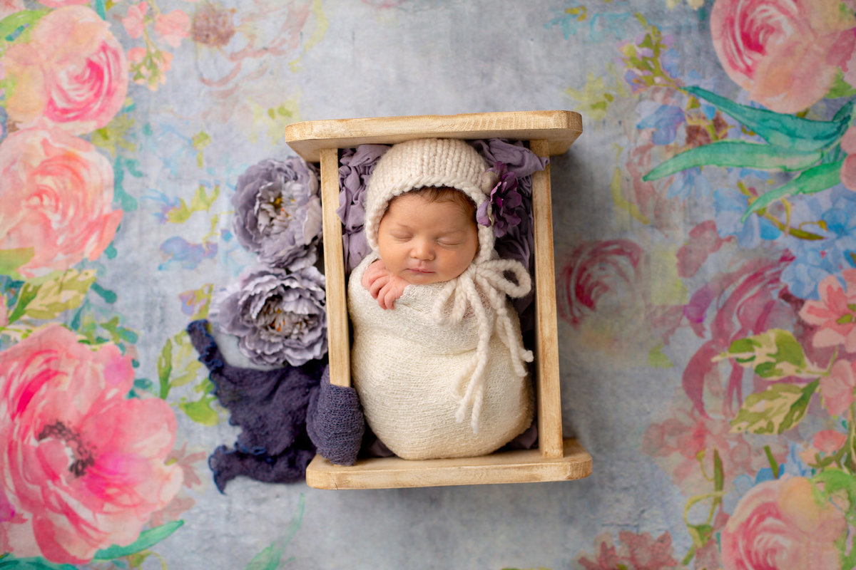 newborn girl swaddled in white lays in a mini cradle against a floral background
