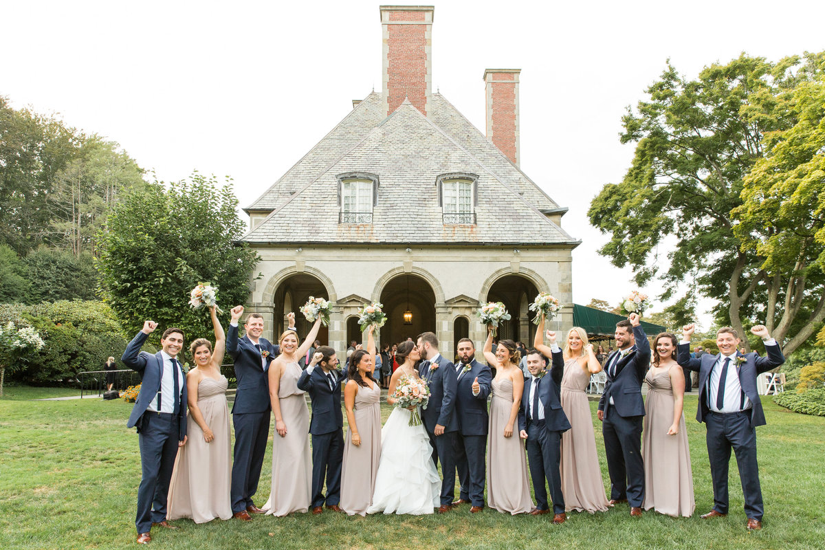 Bride and Groom kiss as the bridal party cheers on the greens at Glen Manor House