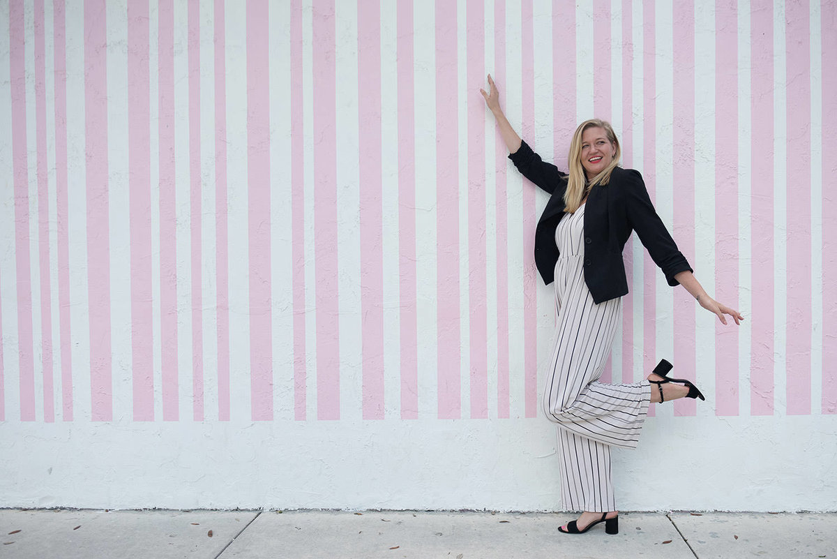 woman posing at mural in miami design district
