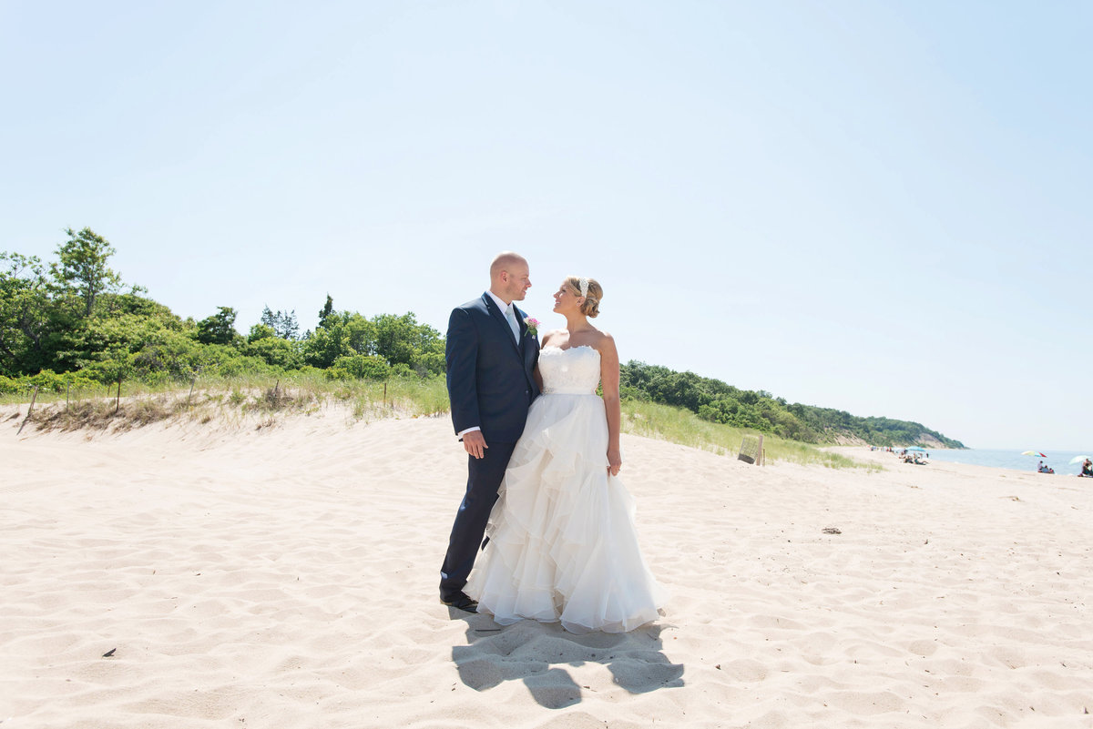 photo of bride and groom looking into each others eyes on the beach from wedding reception at Pavilion at Sunken Meadow