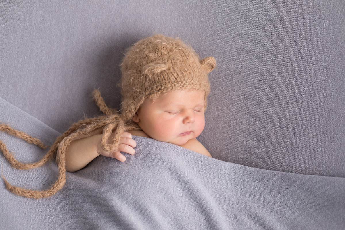 Newborn boy sleeping with teddy bear hat