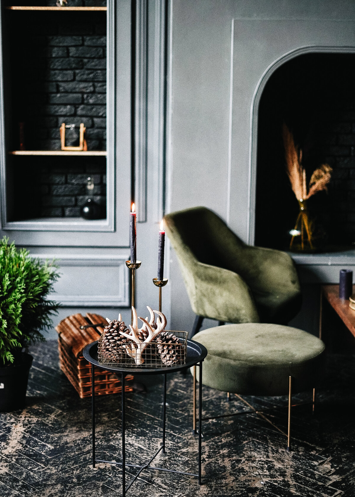Dark grey walls surround a moss green velvet chair in a moody lounge with black candlesticks and pinecones in the foreground.