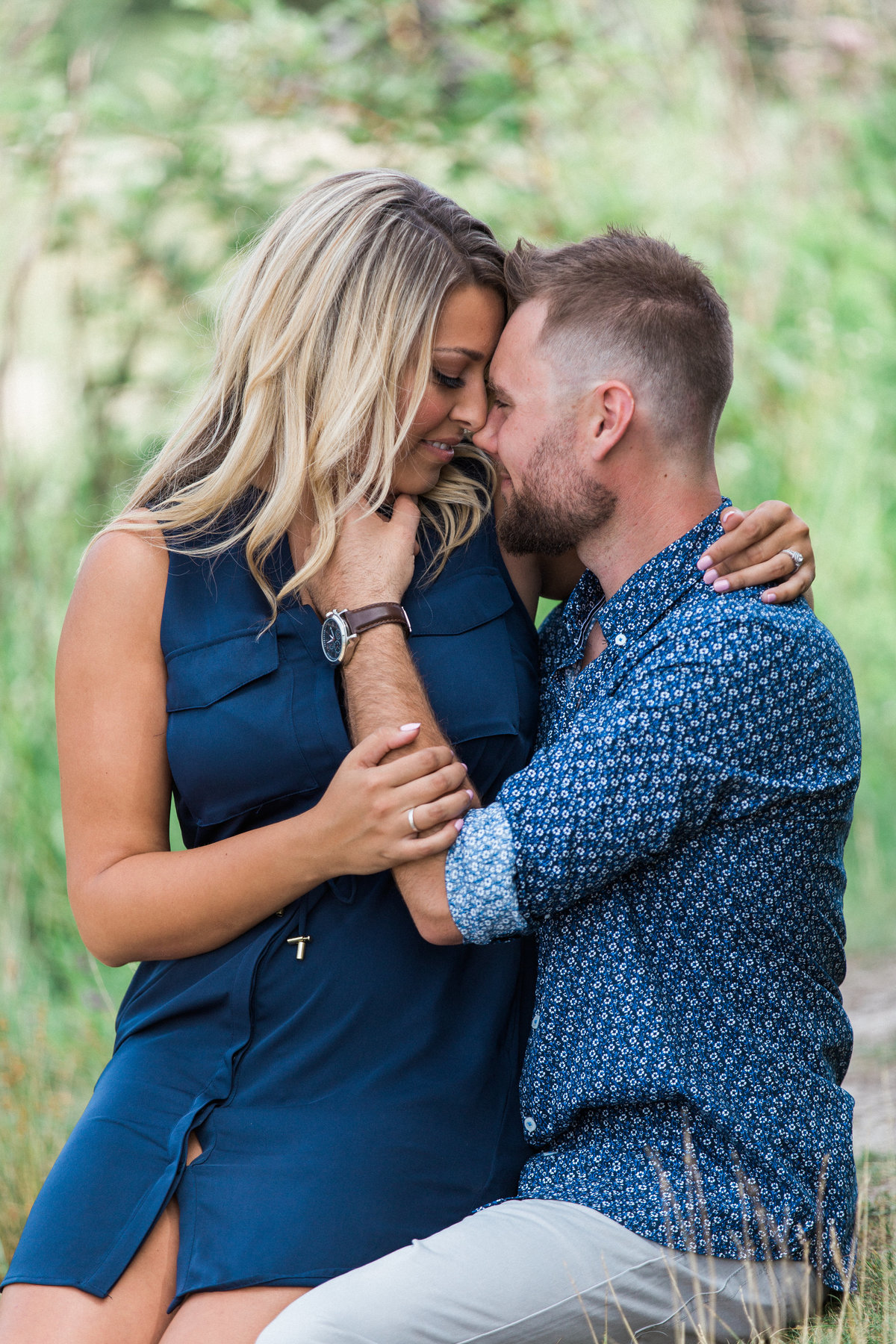 engagement photo of woman sitting on fiances lap