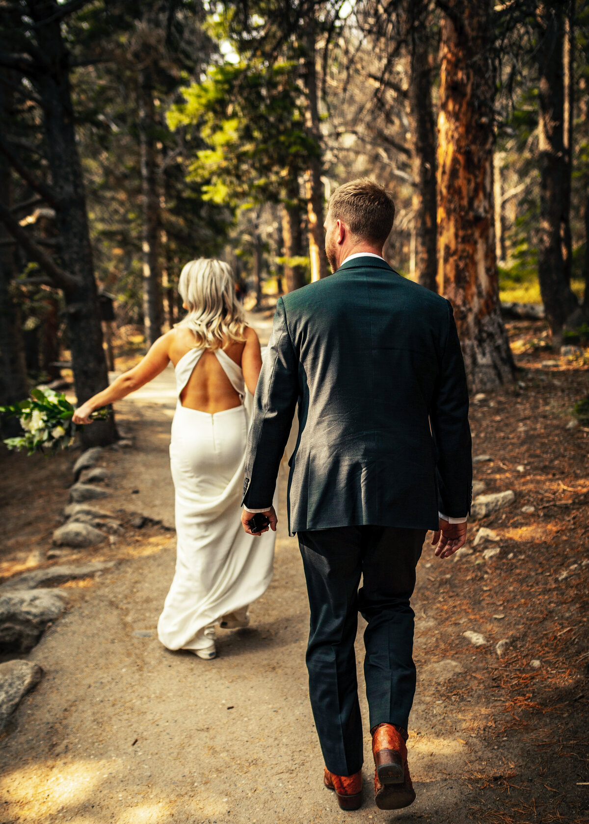 A blonde bride wearing a backless dress walks in front of her groom in a tall forest.