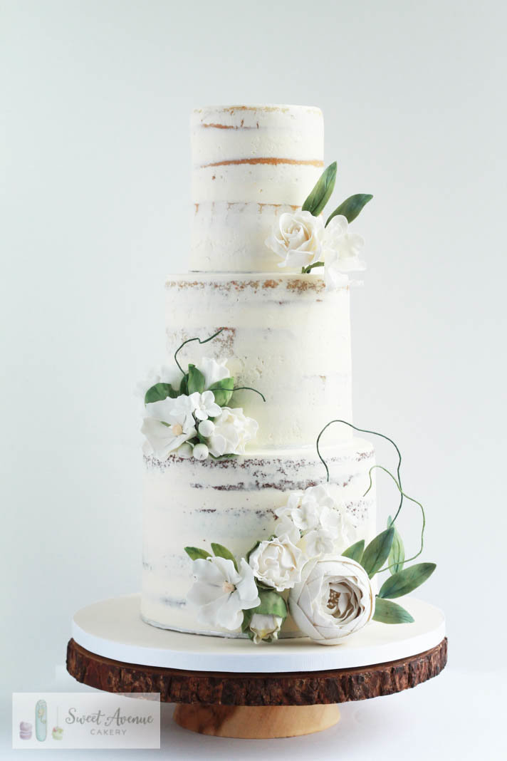rustic semi naked buttercream wedding cake with woodland flowers