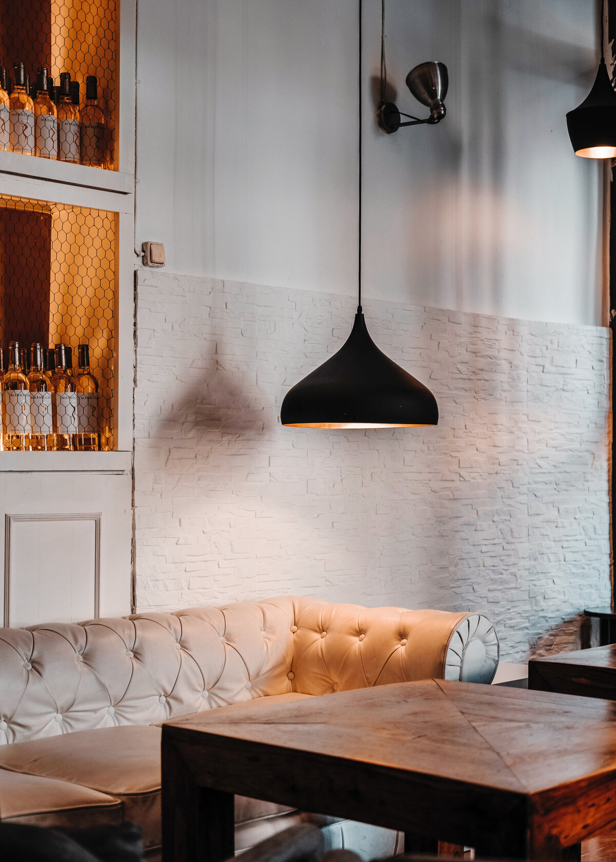 A restaurant is designed with a white chesterfield and a sleek black pendant light.