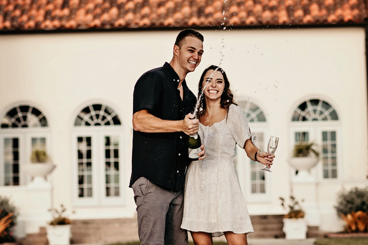 A picture of a couple laughing and celebrating their engagement as the man opens a bottle of champagne that sprays out while the fiancee holds a glass ready to fill up by Garry & Stacy Photography Co - Tampa FL engagement photography