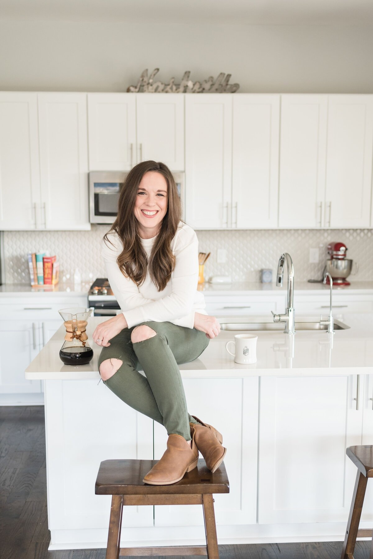 Casual lifestyle headshot of lady sitting on kitchen counter with her feet crossed and resting on a bar stool