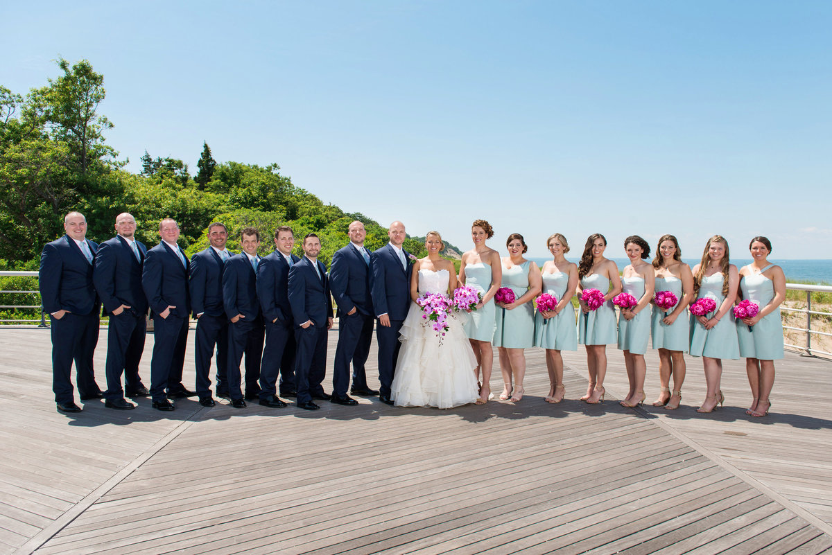 photo of bridal party with bride and groom on the boardwalk from wedding at Pavilion at Sunken Meadow