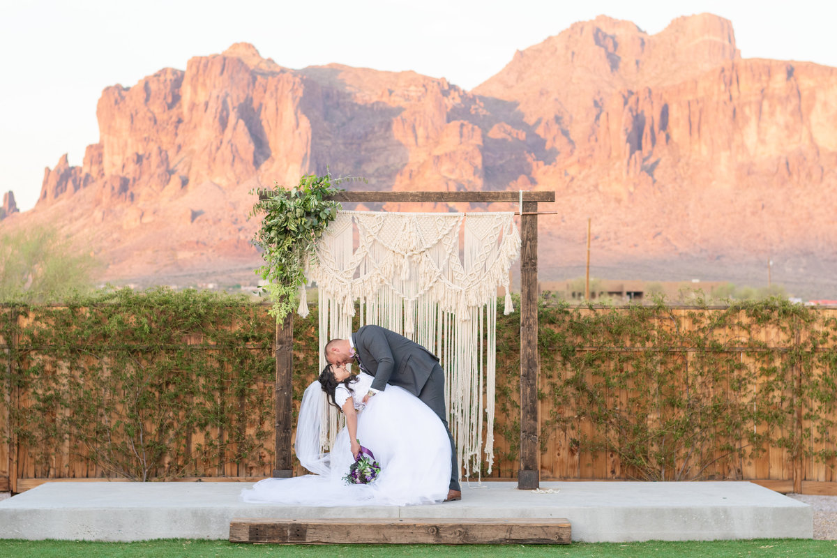 groom dipping bride in front of superstition mountains at the paseo