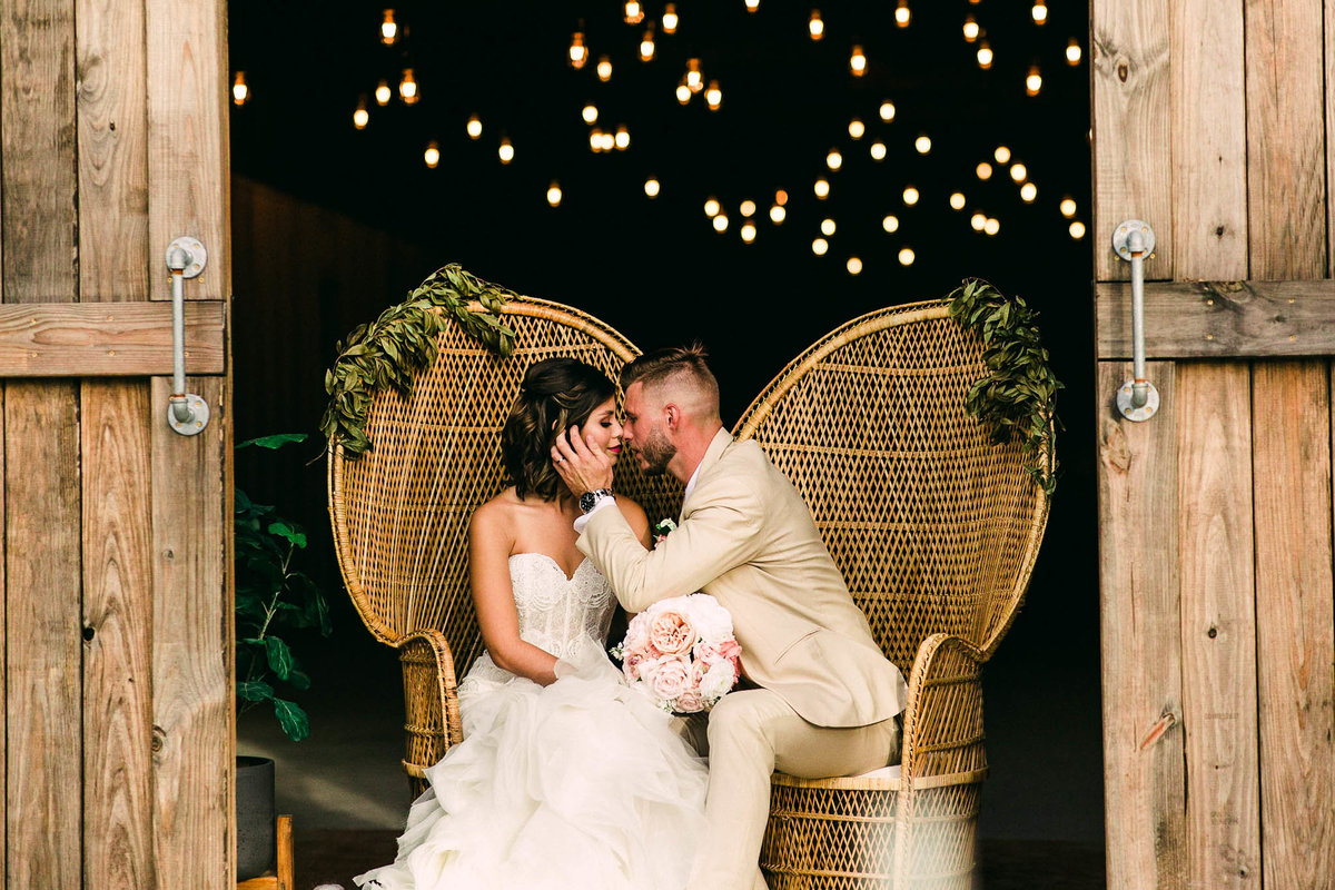 Bride in groom in front of Edison barn lit with twinkling lights