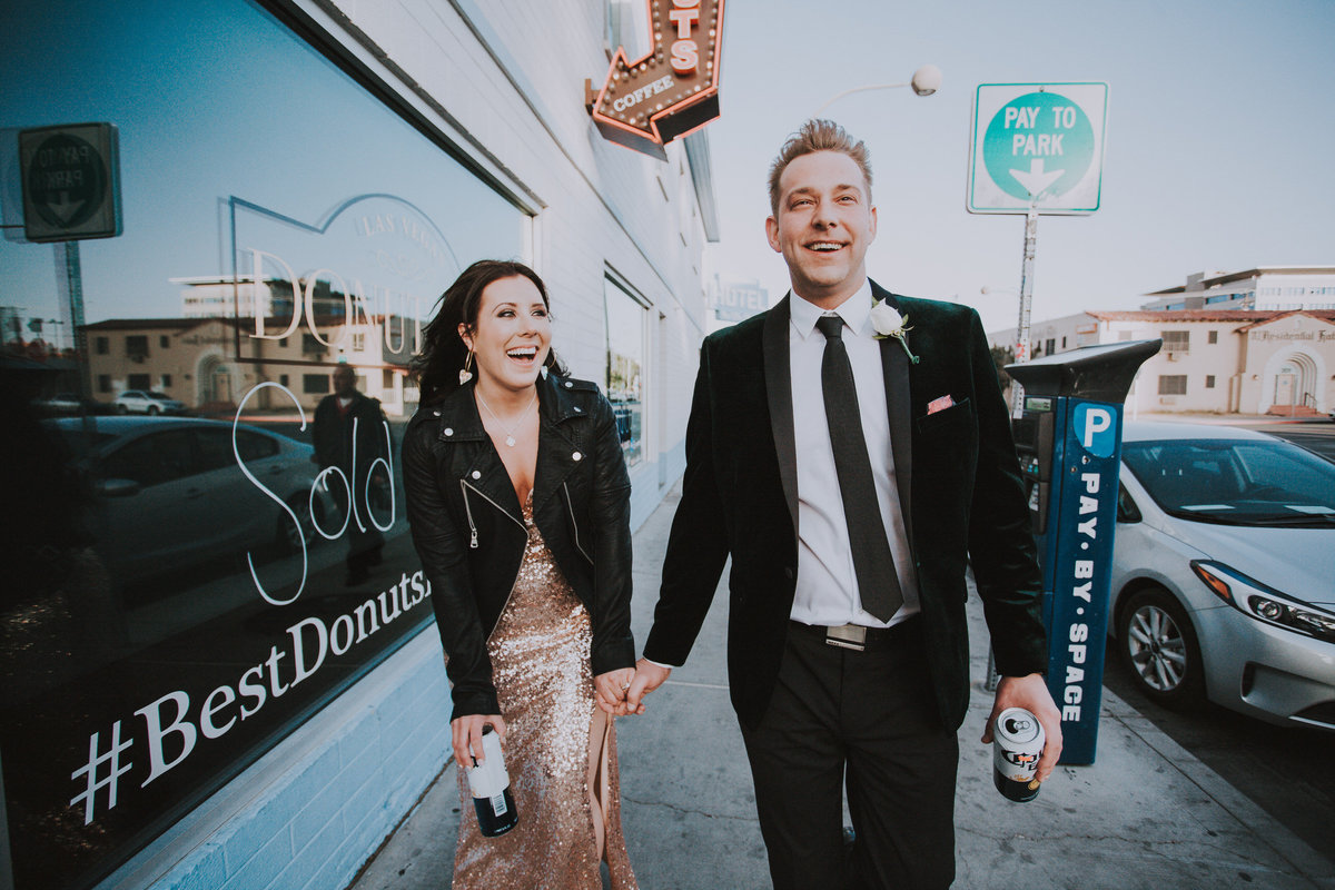 Reno elopement photographers couple walks down sidewalk holding beers