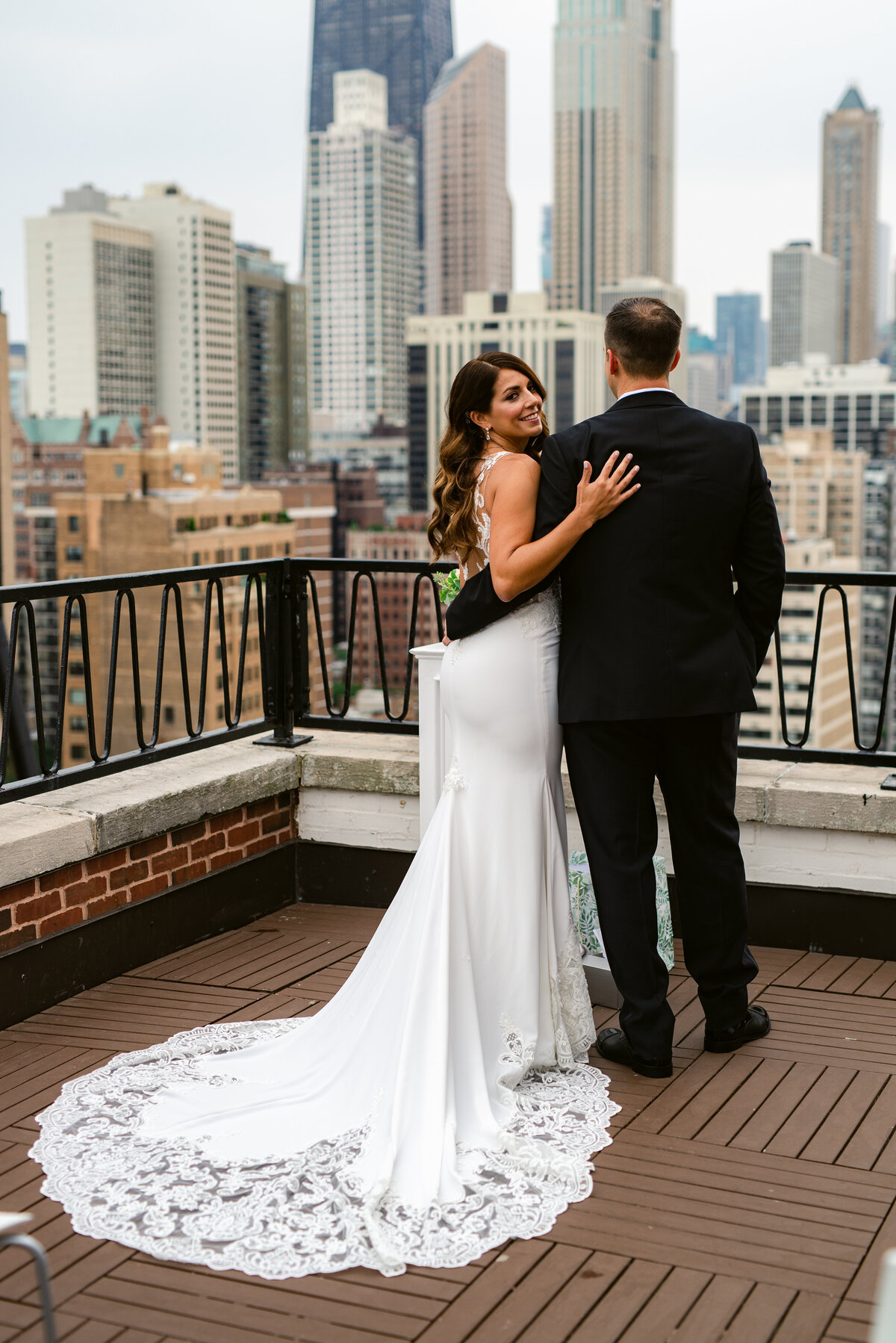 Bride and Groom standing on top of Ambassador Hotel in Chicago. Bride is looking back at photographer, while Groom overlooks the cityscape.
