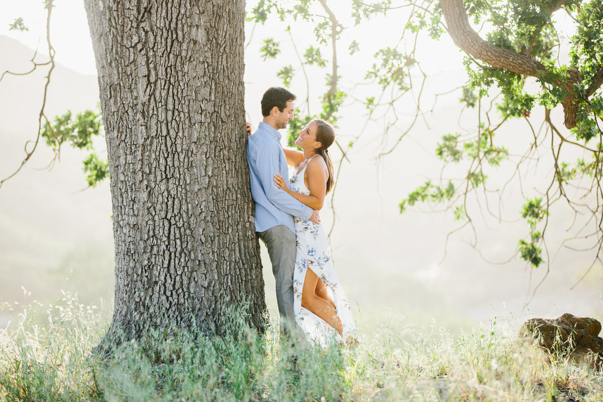 A couple at their engagement session against a big oak tree