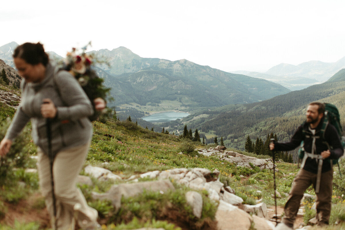 A man and woman hike in the foreground, out of focus, wearing hiking clothes and with a wedding bouquet strapped to one of the packs with a beautiful mountain scenery in the background