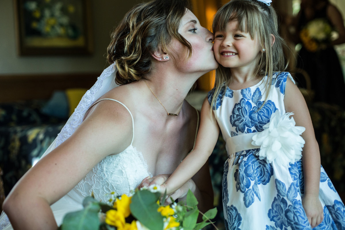 bride kissing flower girl, bride with flower girl