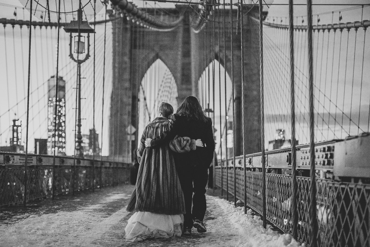 Bride & groom walk on the Brooklyn Bridge after their Brooklyn, NY wedding.