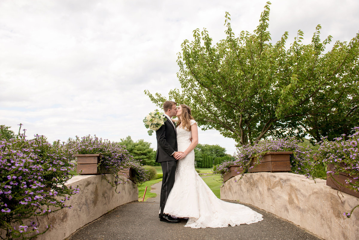 bride and groom kissing photo on bridge at Willow Creek Golf and Country Club