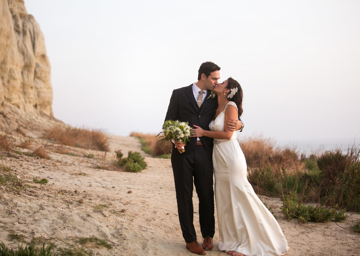 Just married bride and groom embracing outside in San Clemente