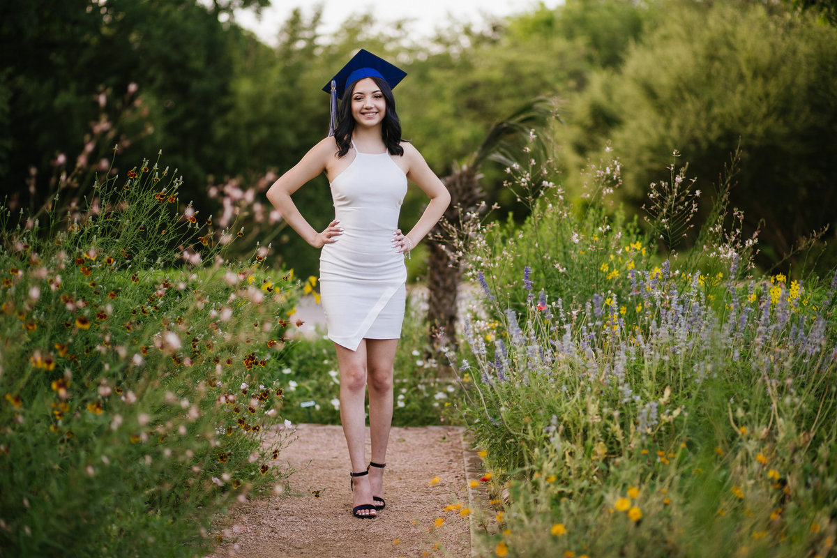 senior high school girl standing in flowers in San Antonio by high school senior photographer