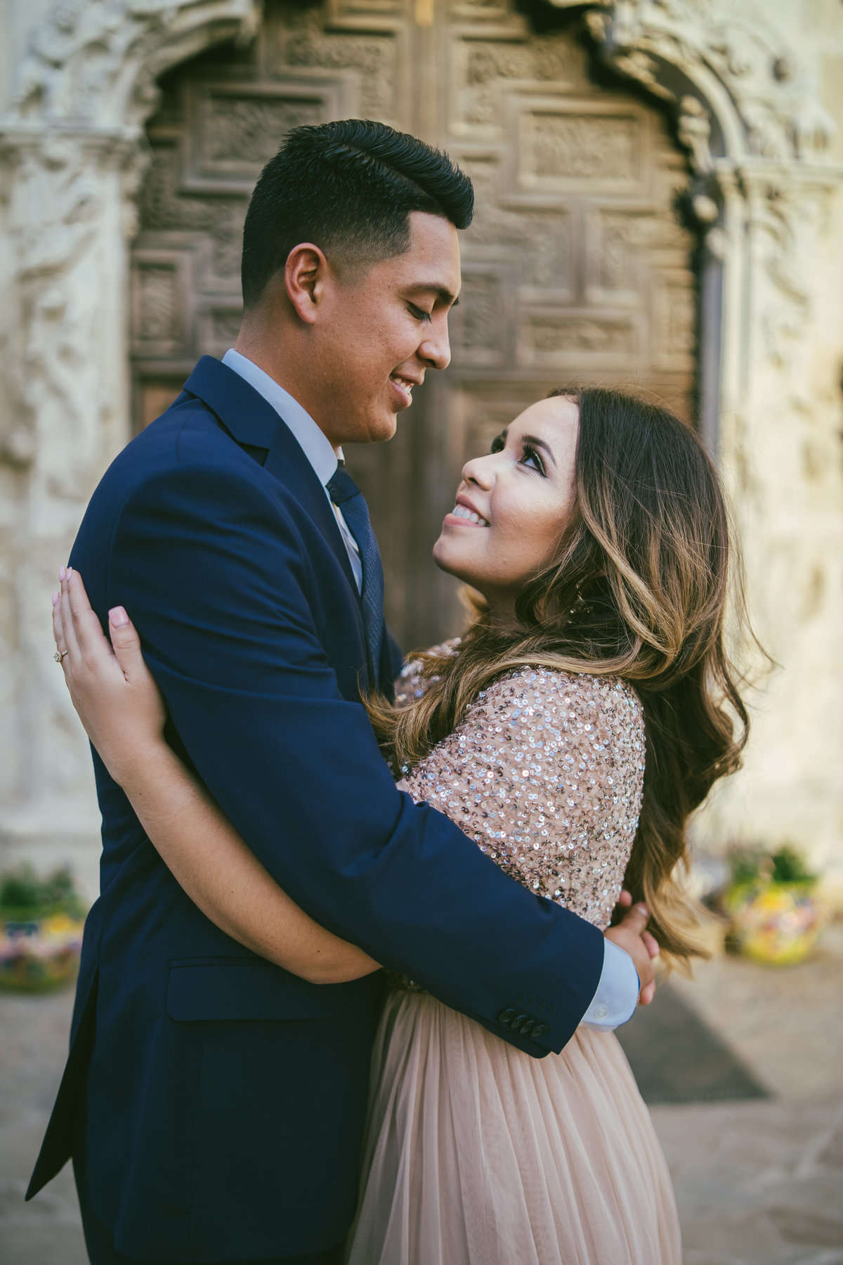Couple embracing in front of Mission San Jose door on their engagement session.