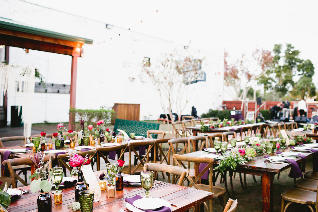 wood farm tables with wood chairs with an eclectic tablescape design