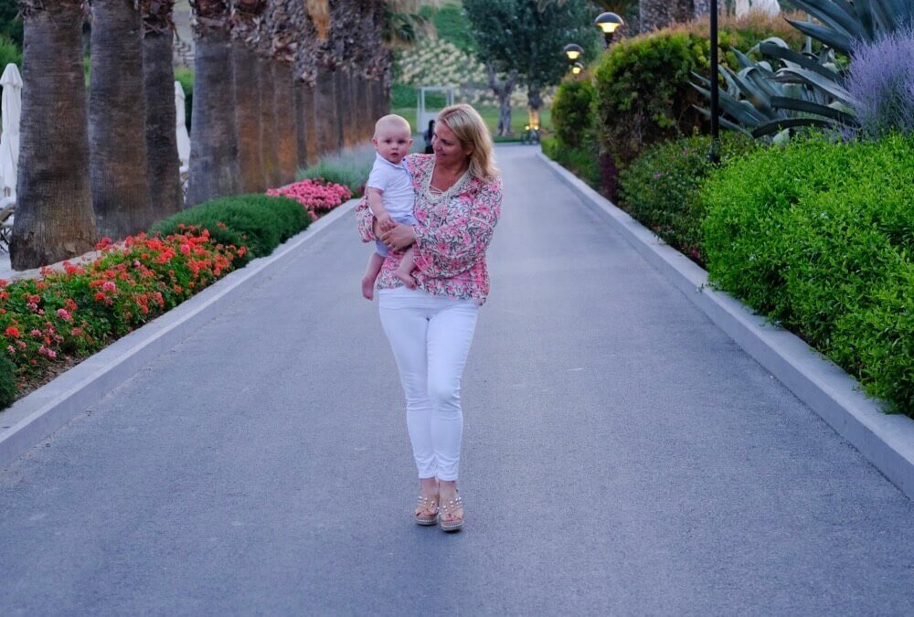 Charlotte holding her son Harry while walking down the road