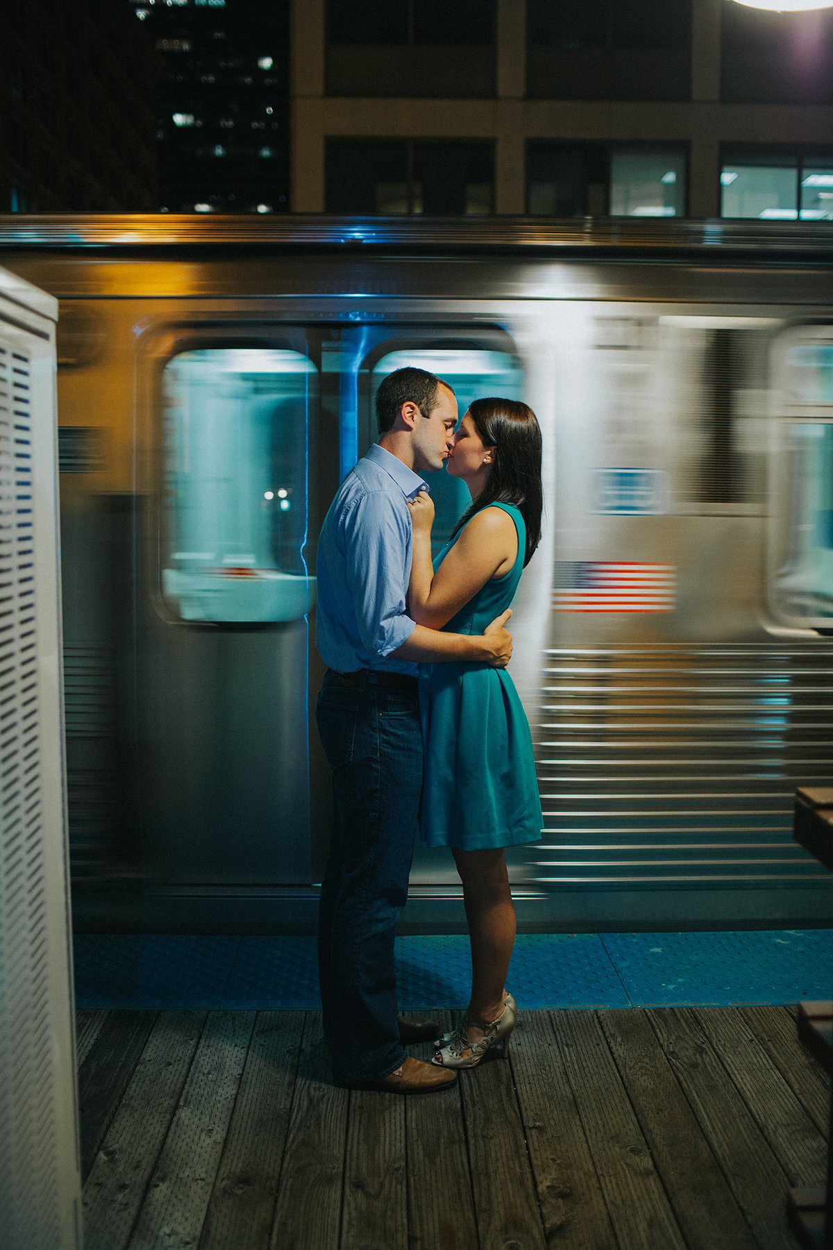 couple kissing in front of a train  in Chicago illinois