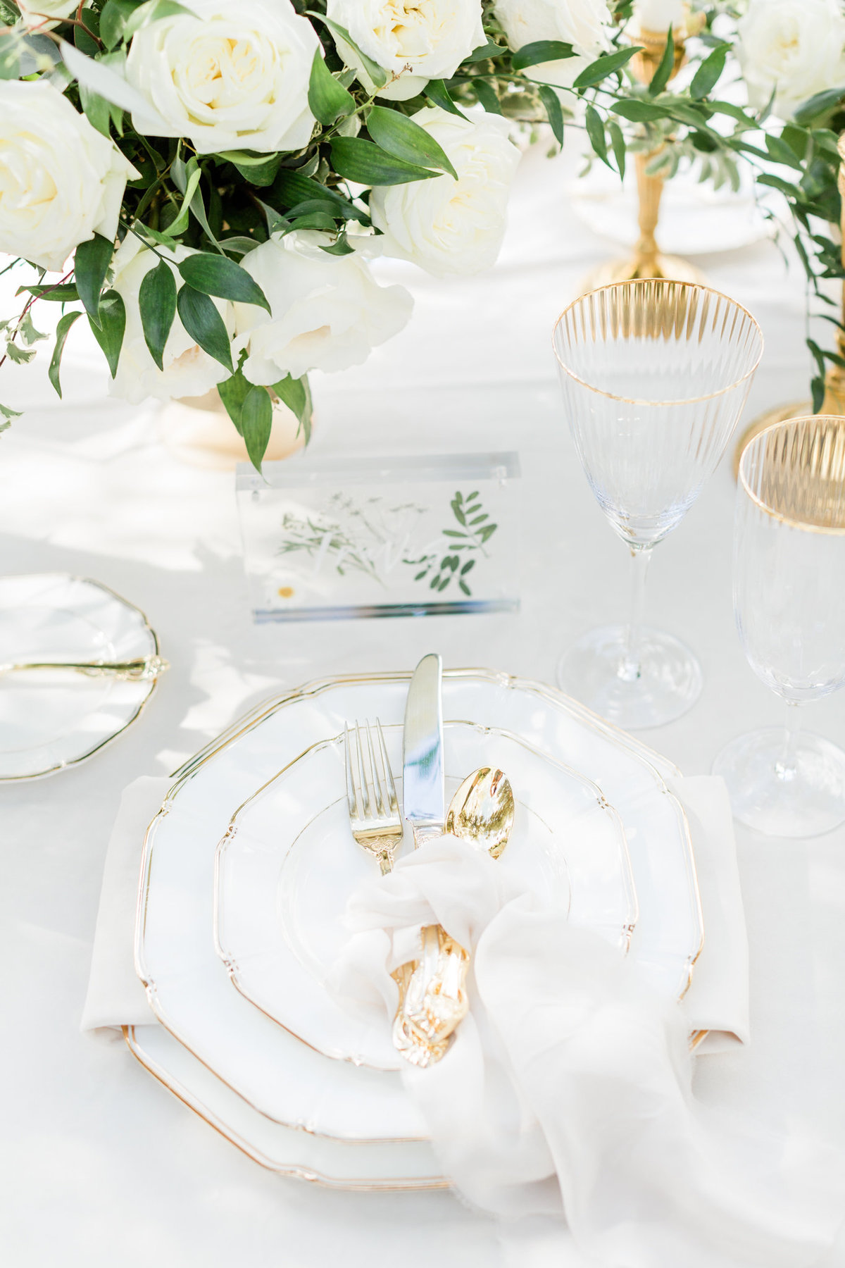 white and gold wedding reception place setting