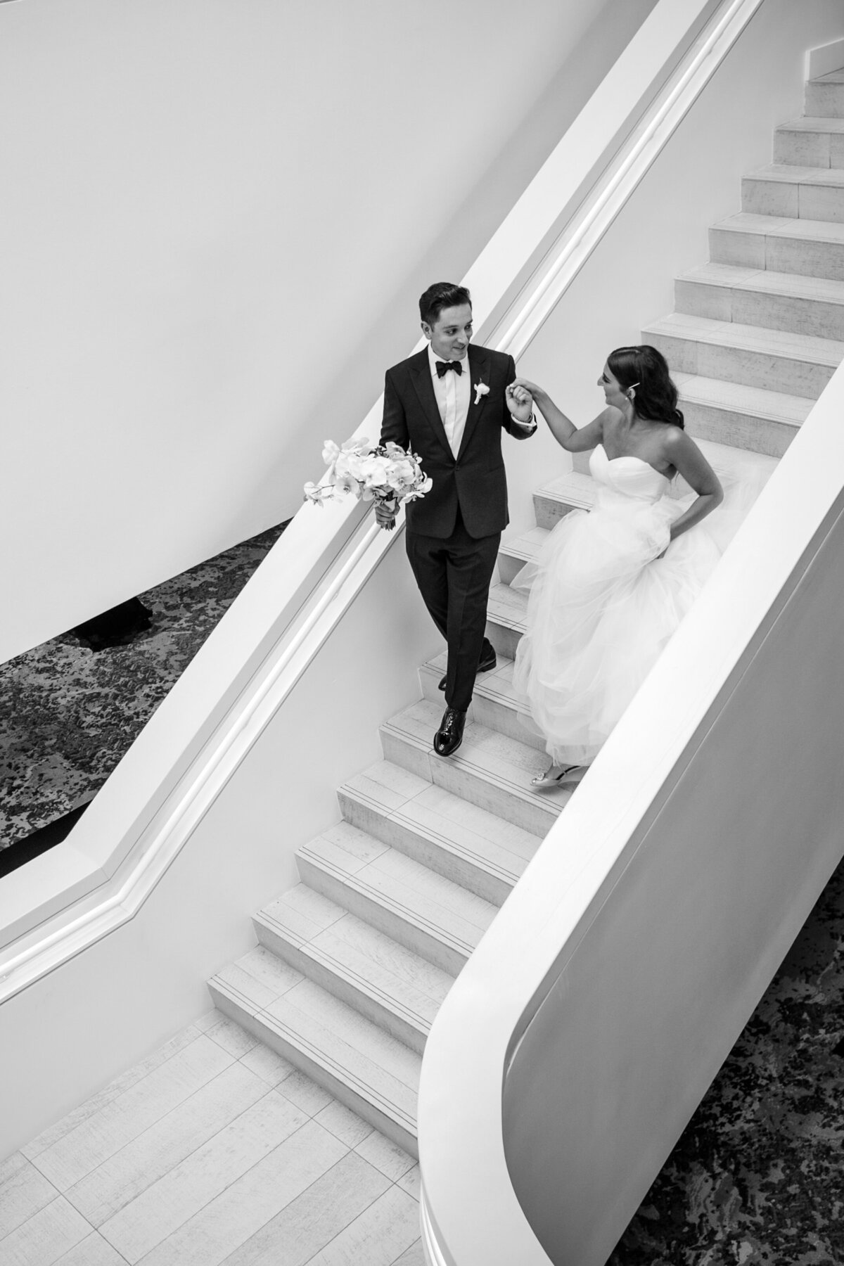 black and white image of a bride and groom walking down the stairs at the W hotel Fort Lauderdale