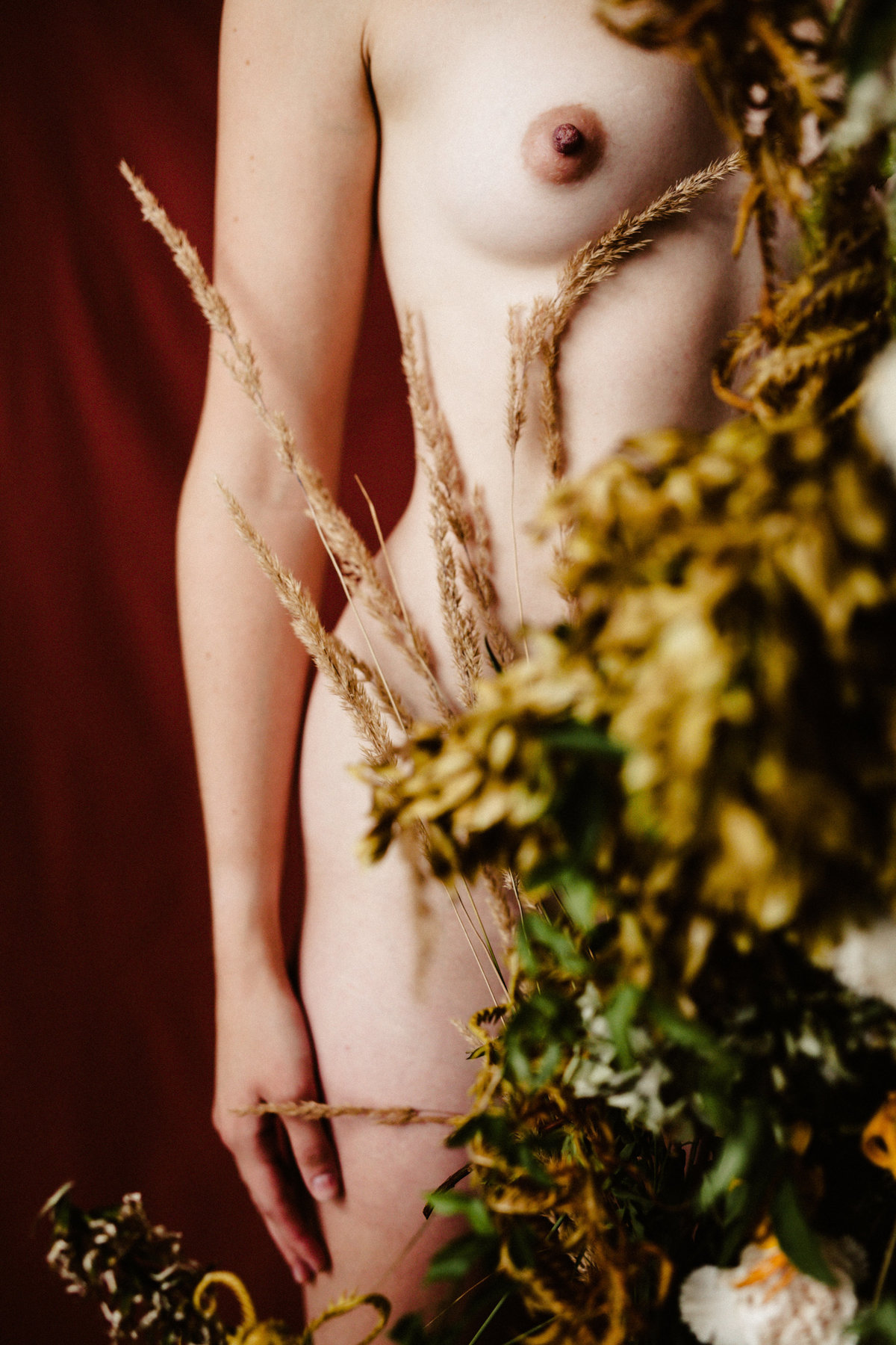 nude woman stands behind custom floral creation tanya val