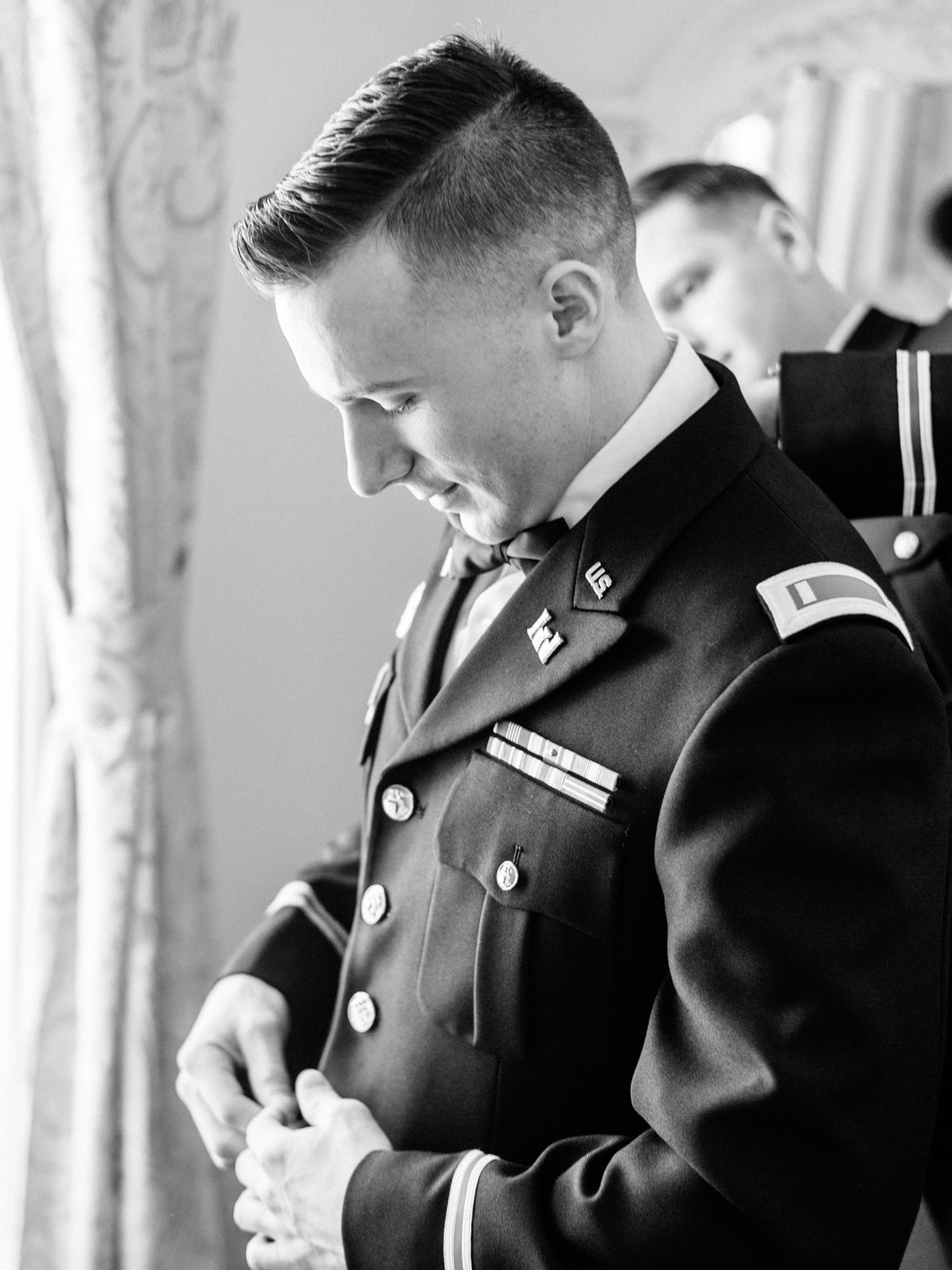 groom putting jacket on