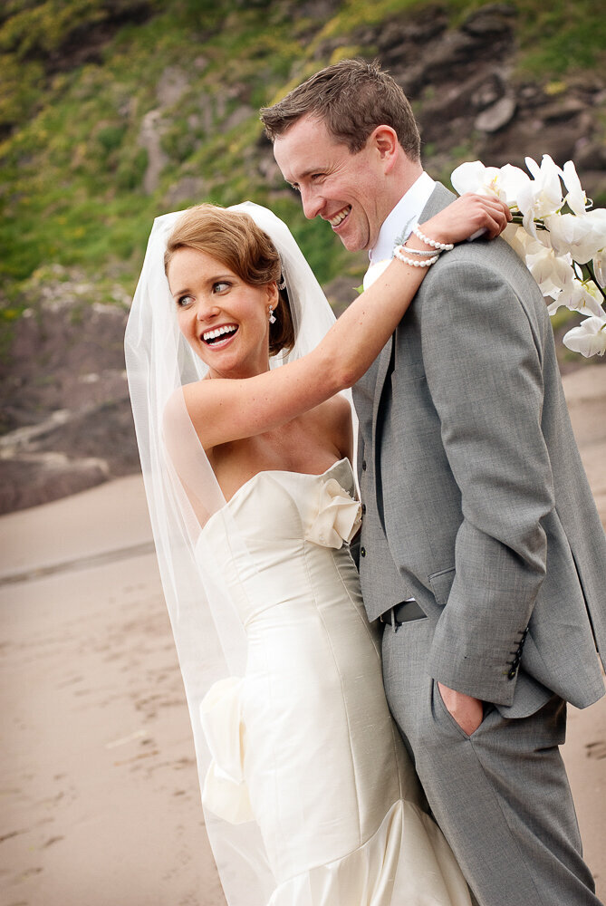 brunette bride wearing a mermaid style wedding dress, holding a white flower bouquet hugging her husband who is wearing a light grey suit with waistcoat, standing on the beach in Kerry