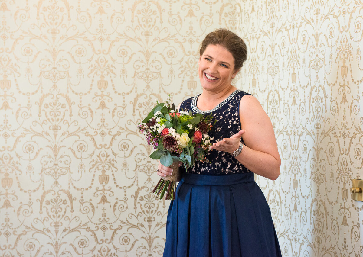 bride in navy wedding dress holding colourful bouquet