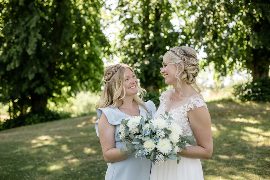 Bride and maid of honor in light blue stand outdoors and smile at each other