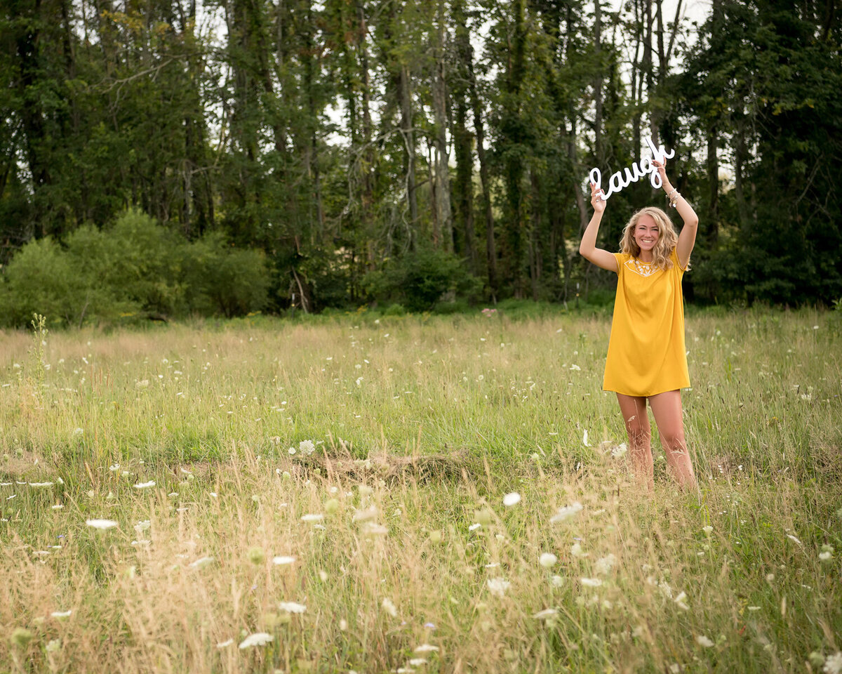 yellow dress senior girl laugh sign open field
