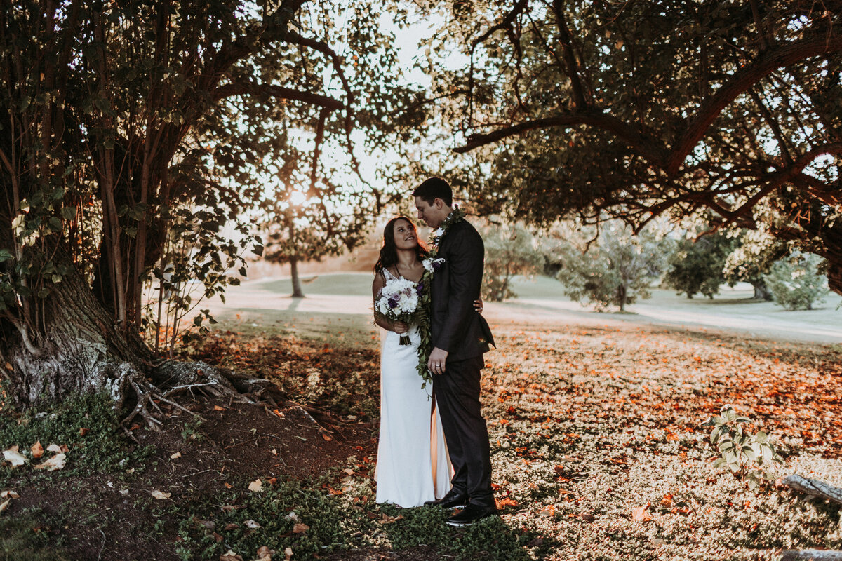 Bride-and-groom-standing-under-tree-with-leaves-that-turned-brown-at-sunset