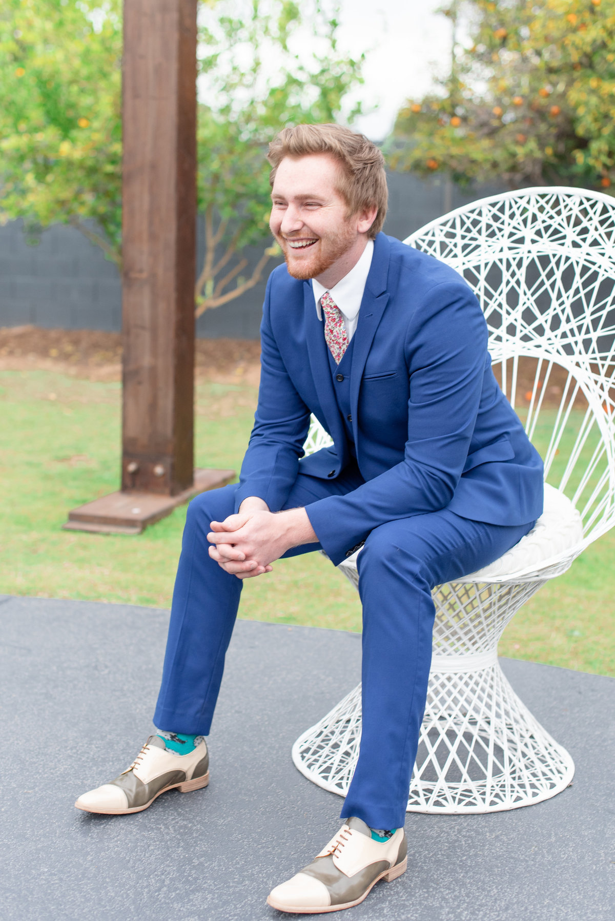 groom sits in white peacock chair and smiles in blue suit