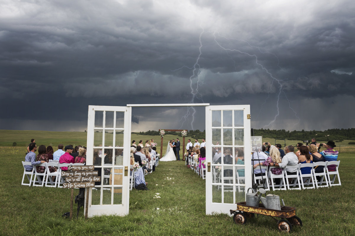 Lighting fills the sky at the weather changes at this wedding